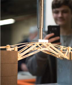 AT THE COLORADO HIGH SCHOOL BRIDGE BUILDING COMPETITION ON FEBRUARY 18, A COMPETITOR'S MODEL FEELS THE STRAIN.